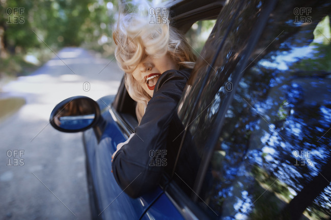 Young adult woman with tousled hair driving car