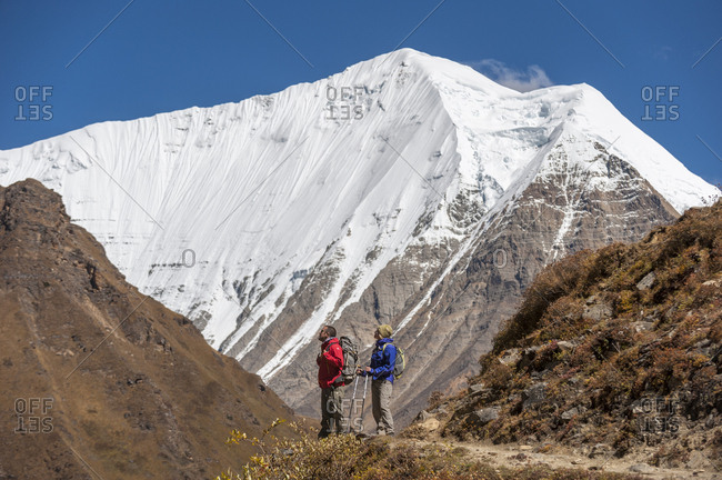 A couple trekking in the Kagmara valley in a remote region of Nepal with a big snow covered mountain in the background