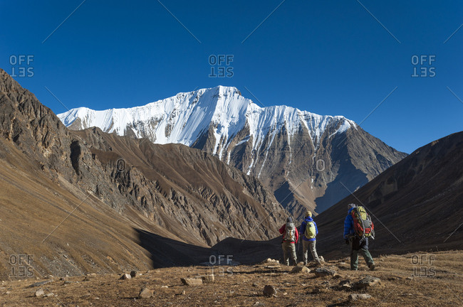 Trekkers walk up the Kagmara valley in Dolpa a remote region of Nepal with views of Lhashama in the distance