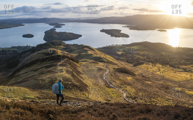 A man hiking down from the top of Conic Hill towards Loch Lomond along The West Highland Way in Scotland
