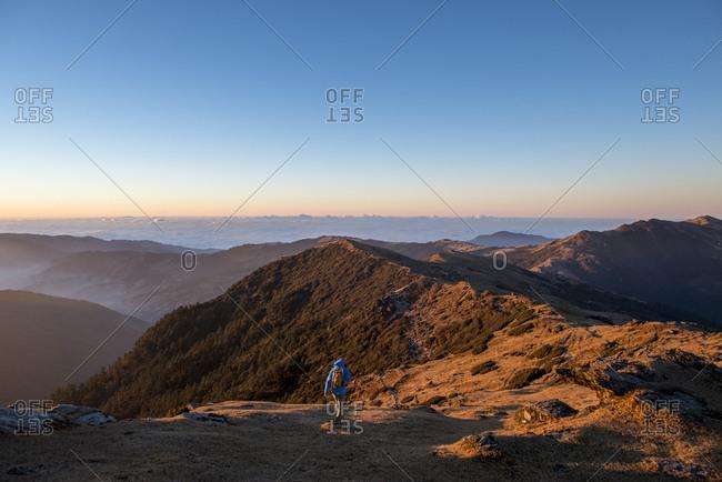 A trekker descends at sunrise on Pikey Peek in the Solukhumbu region of Nepal