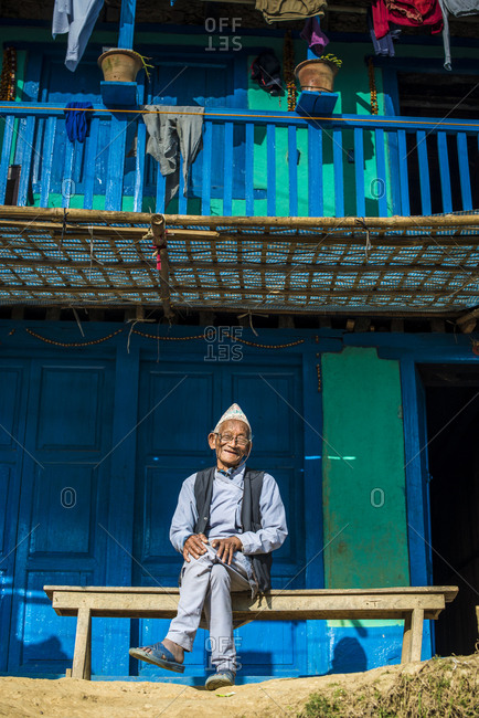 A old Nepali man wearing traditional dress sits outside his house in Diktel