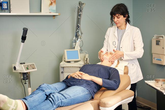 Dermatologist giving client a facial