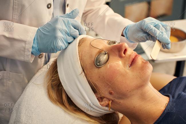Dermatologist applying facial with a tongue depressor