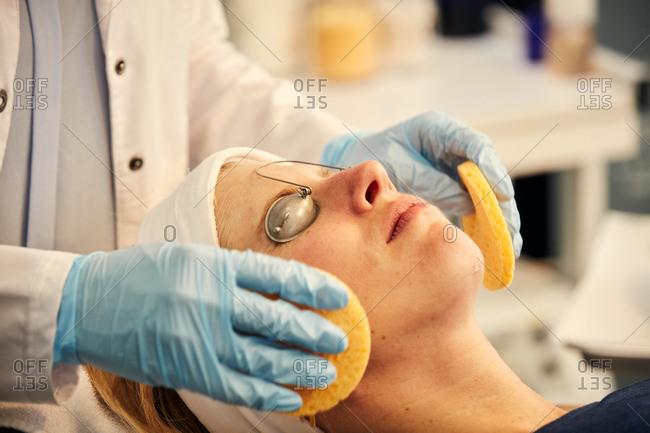 Dermatologist giving client a facial with sponges