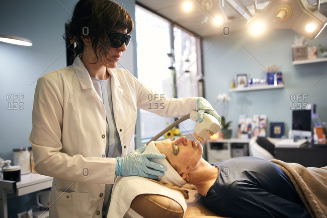 Dermatologist performing a laser procedure on a client's face