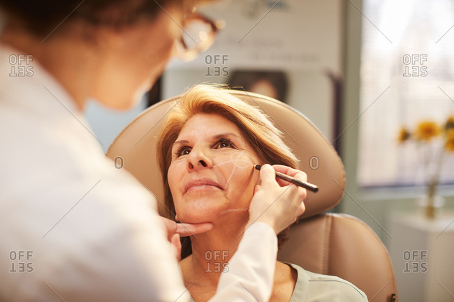 Dermatologist drawing on a client's face before a procedure