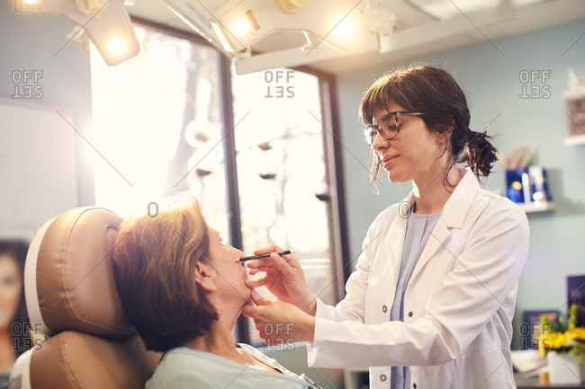 Dermatologist drawing on a patient's face before a procedure