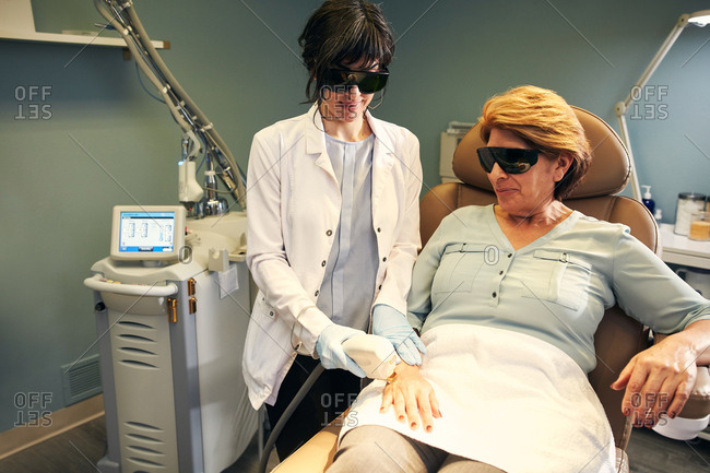 Dermatologist performing a laser procedure on a client's hand