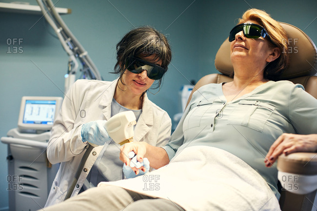 Dermatologist performing an anti-aging laser procedure on a patient's hand