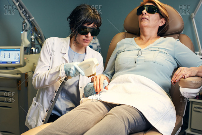 Dermatologist performing an anti-aging laser procedure on a client's hand