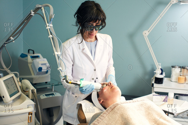 Dermatologist performing a cosmetic procedure with a laser