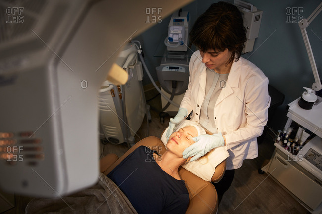 Overhead view of dermatologist giving client a facial