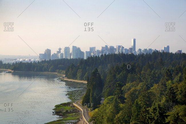 Vancouver, British Columbia, Canada - August, 18, 2014: Skyline seen with Stanley park forest and seawall in foreground