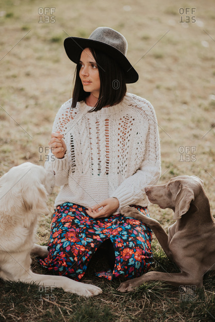 Portrait of a beautiful young woman sitting on ground with two dogs