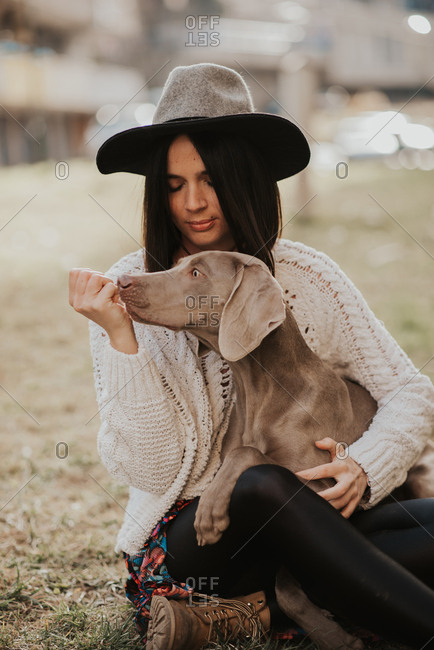 Portrait of a beautiful young woman sitting on ground with her Weimaraner