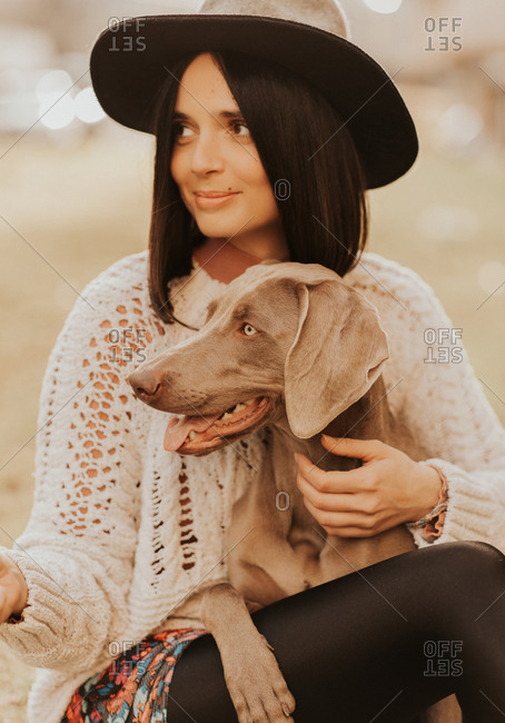 Portrait of a beautiful young woman sitting with her Weimaraner