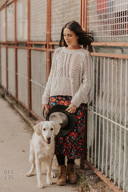 Portrait of a beautiful young woman standing beside her White Golden Retriever