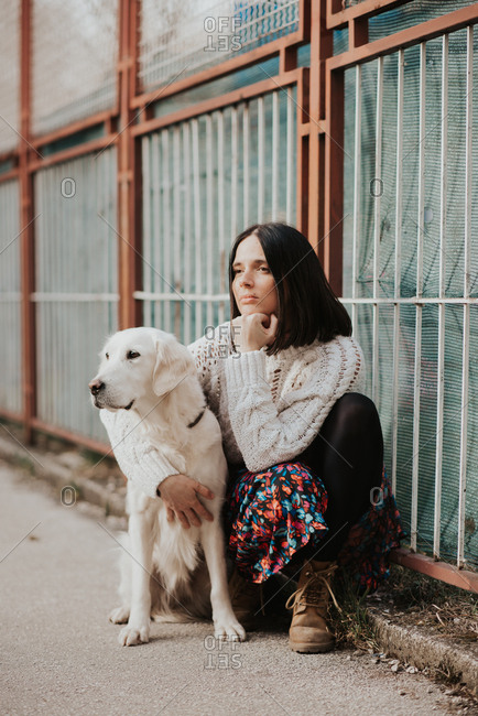 Portrait of a beautiful young woman sitting with her arm around her White Golden Retriever