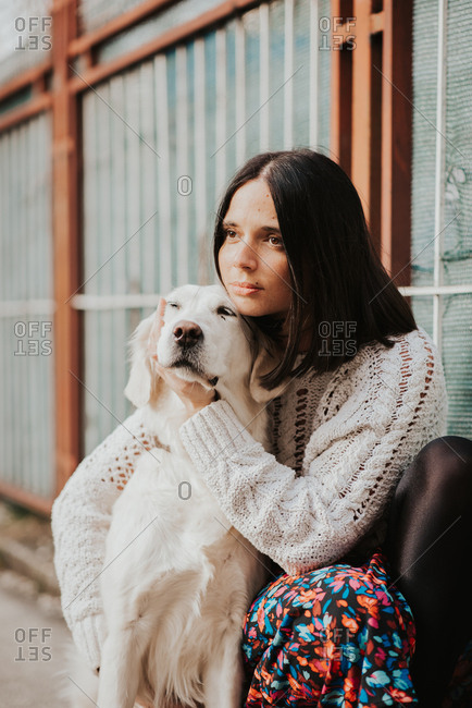Beautiful young woman sitting with her arm around her White Golden Retriever