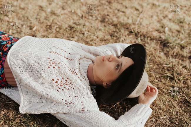 Portrait of a beautiful young woman wearing a stylish hat lying on the ground
