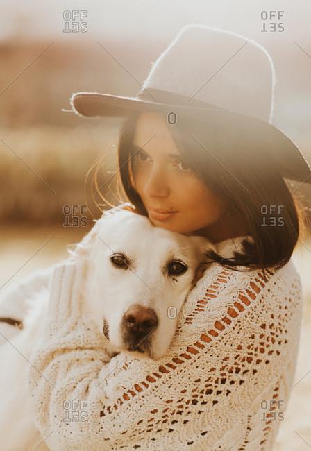 Beautiful young woman embracing her White Golden Retriever