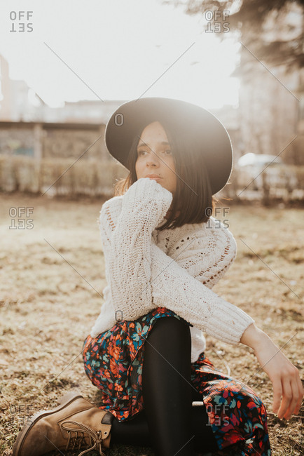 Portrait of a beautiful young woman wearing a stylish hat looking away