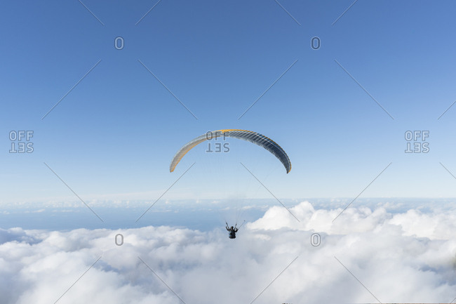 Two humans flying on parachute in blue sky above the clouds