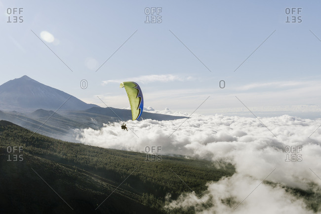 Two humans flying on parachute in blue sky above the clouds and coniferous forest in Teide, Spain
