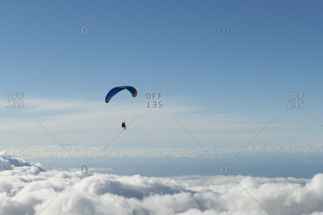 Human flying on parachute in blue sky above the clouds