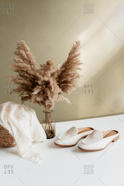 Pampas grass, white shoes, and basket against green wall.