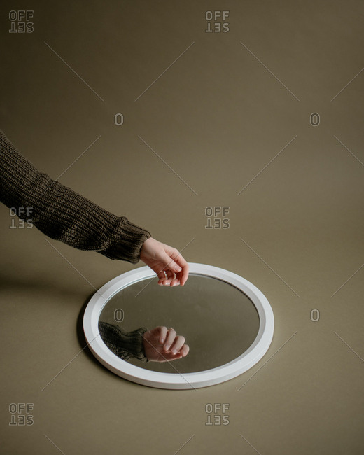 Hand hovering round mirror in green studio.