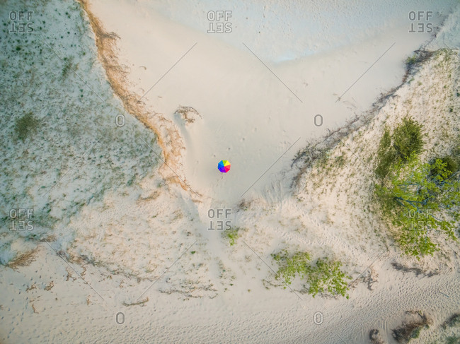 Aerial view of a person holding colorful umbrella at glen arbor beach, Michigan, USA.
