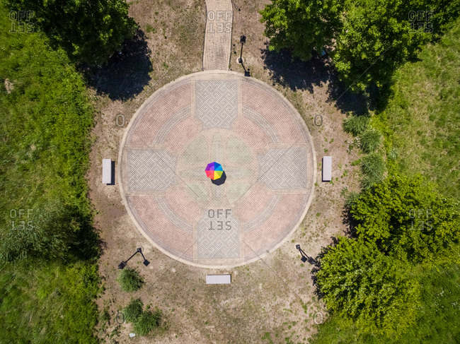 Aerial view of person holding colorful umbrella on pebble background, USA.