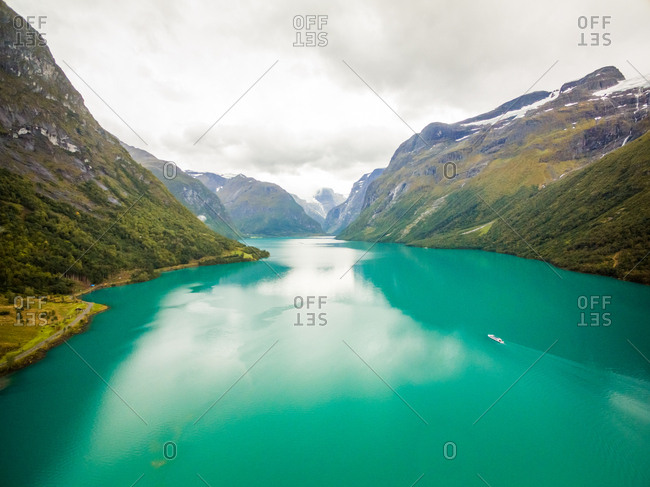 Aerial view of small boat sailing at calm fjord, Norway.