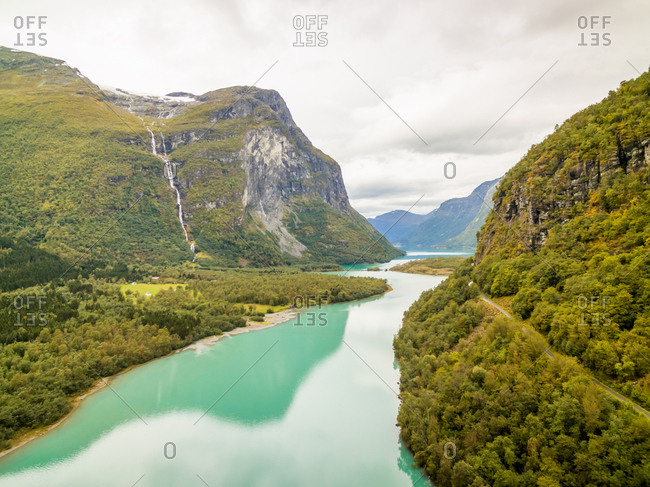 Aerial view of calm fjord crossing chain of tall mountains, Norway.