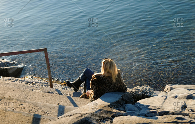 Fashionable woman sitting on stone stairs by the water