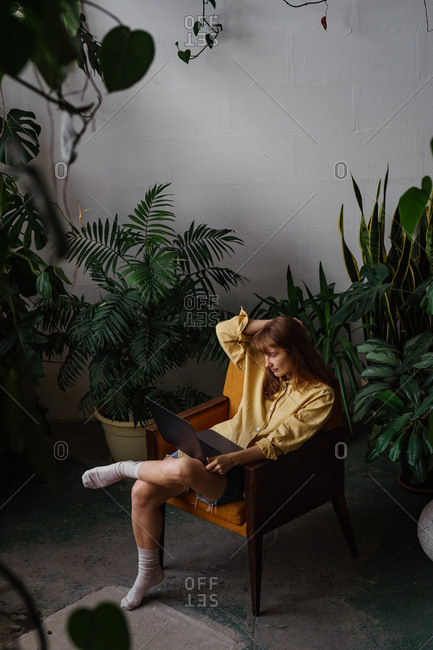 Portrait of young woman with ginger hair working on a laptop sitting in a room full of plants