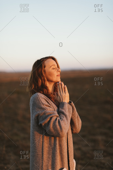 Woman embracing the sunset alone in an open field