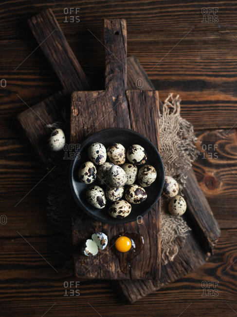 Quail eggs on dark ceramic plate over brown wooden background, view from above