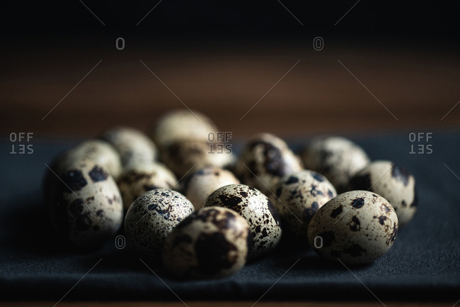 Quail eggs on dark cloth over brown wooden background, close-up view