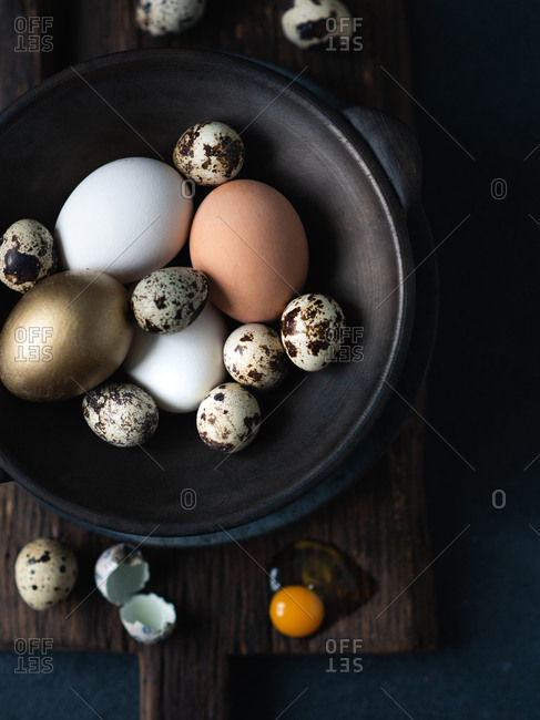 Easter eggs in dark ceramic bowl over dark background, view from above