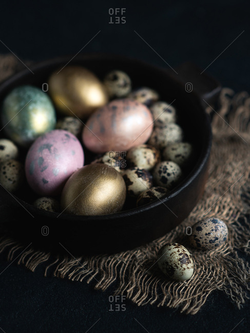 Colorful Easter eggs in dark ceramic bowl over dark background