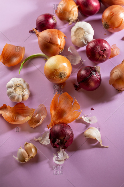 Onions  and garlic on pink background
