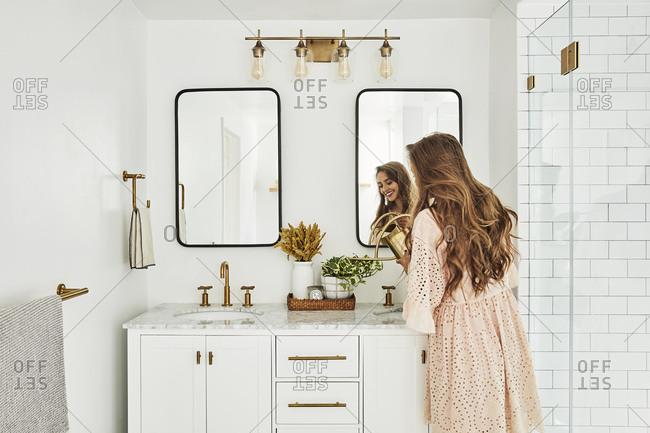 Los Angeles, California - November 21, 2018: Woman watering plants in bathroom