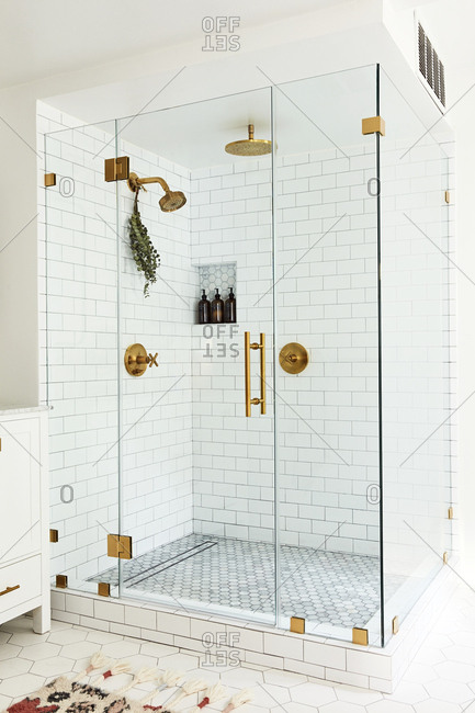 Los Angeles, California - November 21, 2018: Large walk-in shower with subway tiles and bronze fixtures
