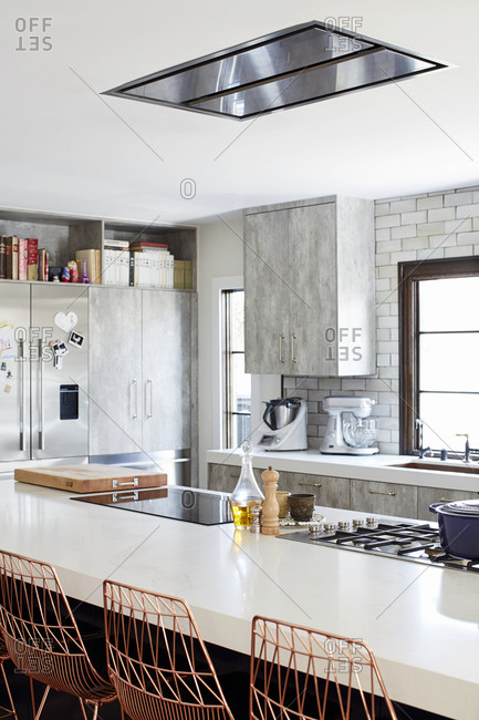 Los Angeles, California - November 29, 2018: Modern kitchen with a large white island and copper chairs