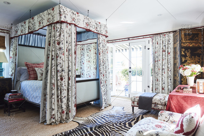 Los Angeles, California - October 5, 2016: Bedroom with floral wallpaper and canopy around bed that opens to patio