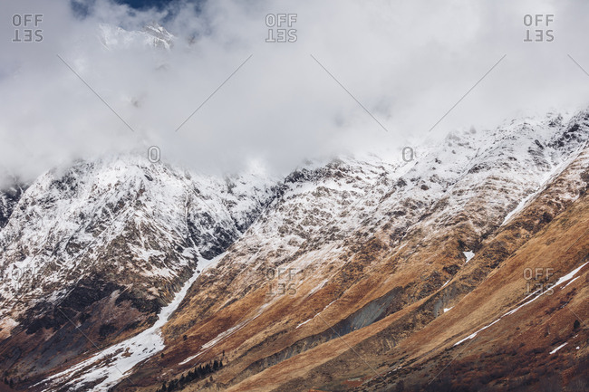 Clouds surround snowy peaks in the Pyrenees mountains