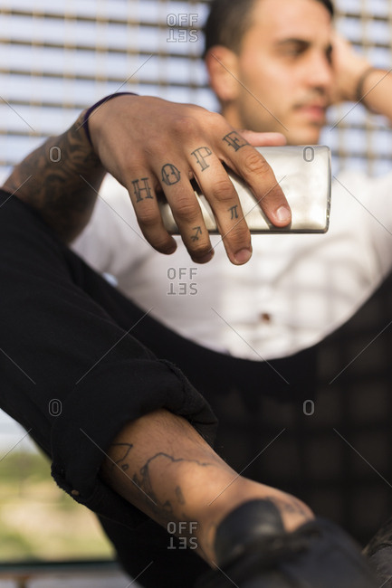 Cropped image of stylish man holding smart phone with hope tattooed on knuckles